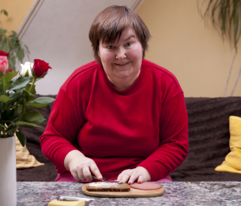 mentally handicapped woman is making up a sandwich